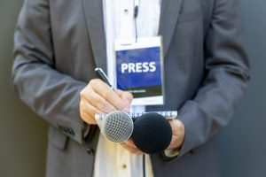 Male,Journalist,At,News,Conference,Or,Media,Event,,Holding,Microphone,
